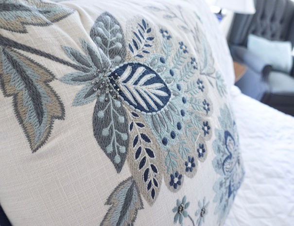 closeup of the floral pillow on white bedspread in the Bluebonnet Room
