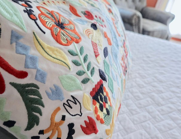 closeup of pillow detail on white bedspread in Bob Bunker Room