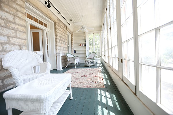 upstairs enclosed porch with white wicker furniture overlooking Main Street