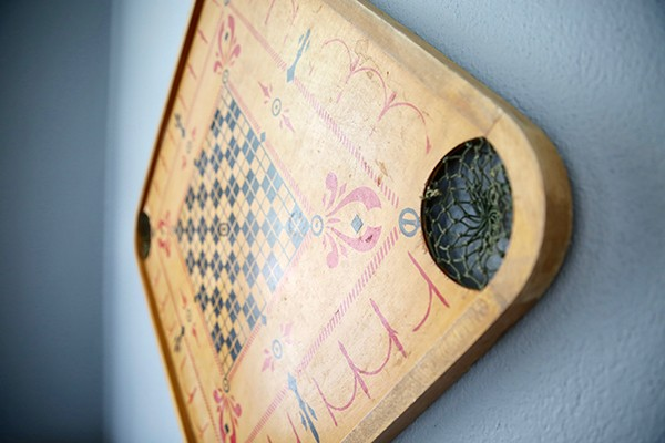 antique checkers game board hanging on wall of living room