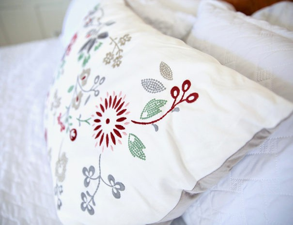 closeup of floral pillow on white bedspread in the Chisholm Trail room